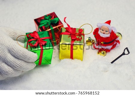 Close up hand, Santa claus holding gift box on the snow with snow bucket on winter background. Delivering happy holidays. Use for wallpaper.