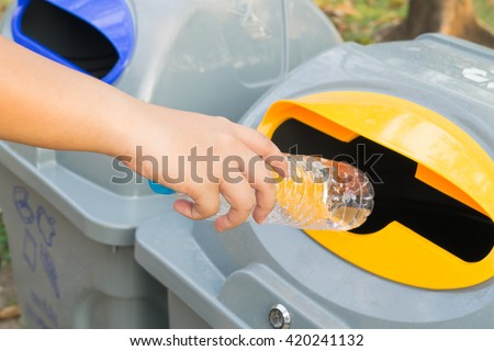 Close up hand throwing empty plastic bottle into the trash - stock photo