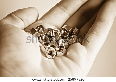 close up hand with bolts and nuts