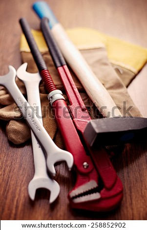 Close up Hand Working Tools like Open Ended and Pipe Wrenches, Cross Pein Sledge Hammer and a Pair of Gloves on Top of a Wooden Table. - stock photo