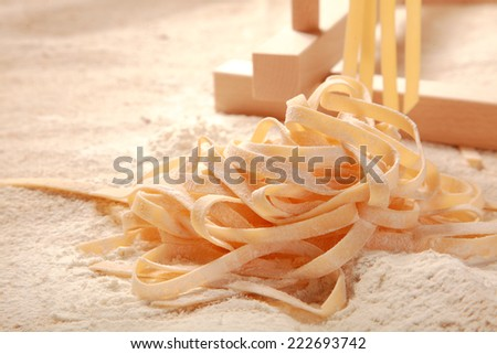 Close up Handmade Raw Fresh Italian Egg Pasta on Flour. Commonly Known as Fettuccine - stock photo