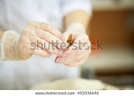 Close-up hands in rubber gloves cut off ampoule head with cutter.