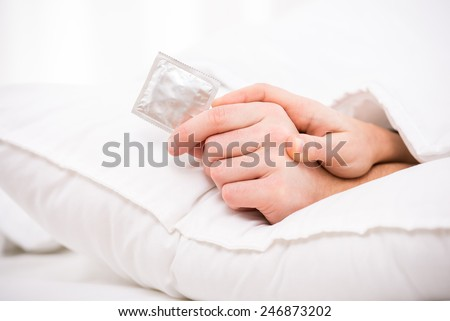 Close-up hands of a couple in bed are holding a condom. - stock photo