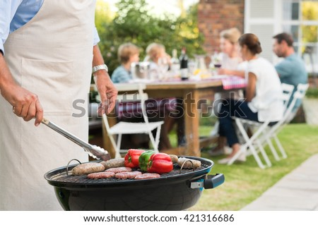 Close up hands of a senior man barbequing in the garden with family in background. Grandfather cooking on grill. Man cooking hamburgers, sausages and peppers with barbeque. - stock photo