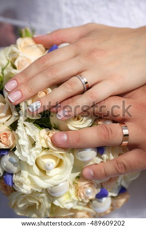 Close up  hands of bride and groom with wedding bouquet and golden rings