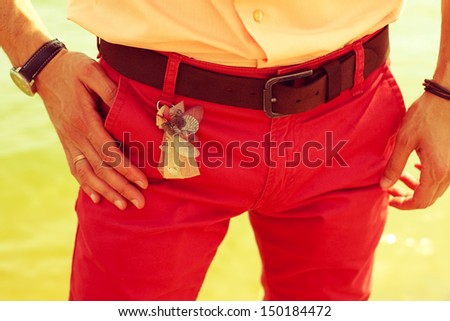 Close up hands of young married hipster in red jeans. Stylish trendy clothes. Peach and red colors. Vintage style. Outdoor shot