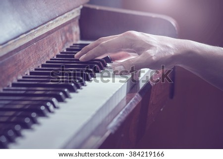 close up hands on the key of the piano,cool tone - stock photo