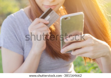 Close up hands using mobile smart phone and holding credit card outdoor, Online shopping, - stock photo