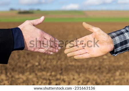 Close up Handshake between businessman and farmer - stock photo