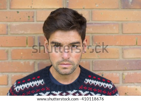Close up handsome man leaning against brick wall and looking seriously at the camera - stock photo