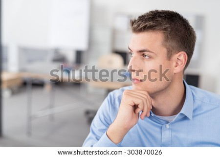 Close up Handsome Young Businessman with Hand on his Chin, Looking Into the Distance with Pensive Facial Expression - stock photo