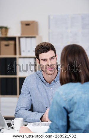 Close up Handsome Young Office Man Talking to his Female Co-worker While Sitting at his Worktable. - stock photo