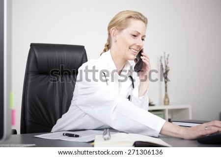 Close up Happy Adult Female Doctor in Medical Suit at her Office Calling Someone Through Telephone - stock photo