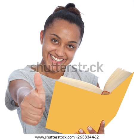 Close up Happy Asian Indian Girl Holding a Book and Showing Thumbs Up Hand Sign While Looking at the Camera. Isolated on White Background