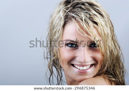 Close up Happy Attractive Young Woman with Wet Blond Hair, Looking at the Camera with Toothy Smile Against Gray Background with Copy Space.