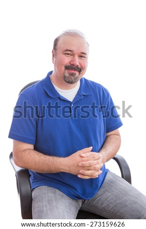 Close up Happy Bearded Adult Man in Blue Shirt Sitting on a Single Chair with Hands Crossed Over her Belly, Looking at the Camera with Admiration. Isolated on White Background.