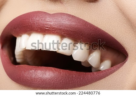 Close-up happy female smile with healthy white teeth, bright magenta lips make-up. Cosmetology, dentistry and beauty care. Macro of woman's smiling mouth  - stock photo