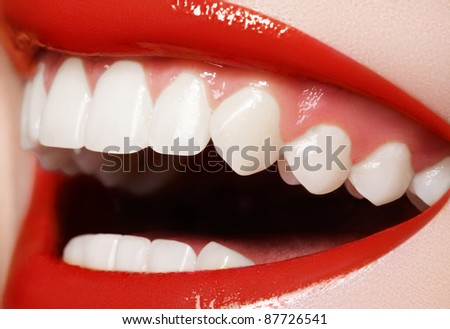 Close-up happy female smile with healthy white teeth, bright red gloss lips make-up. Cosmetology, dentistry and beauty care. Macro of woman's smiling mouth - stock photo