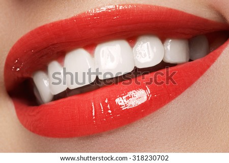 Close-up happy female smile with healthy white teeth, bright red lips make-up. Cosmetology, dentistry and beauty care. Macro of woman's smiling mouth - stock photo