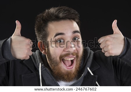 Close up Happy Goatee Young Man with Mouth Open, Wearing Jacket, Showing Thumbs Up Sign While Looking at the Camera. Isolated on Black Background - stock photo