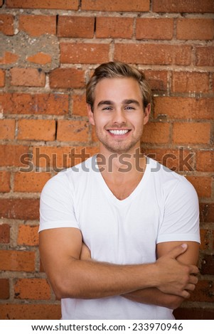 Close up Happy Handsome Young Man in Casual White Shirt Looking at Camera with Crossed Arms on a Brick Wall Background. - stock photo