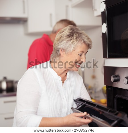 Close up Happy Matured Housewife Cooking Something in Oven for Dinner at the Kitchen. - stock photo