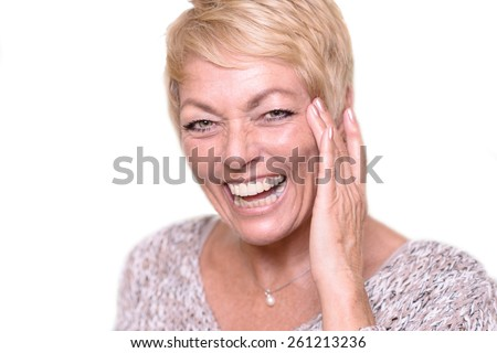 Close up Happy Middle Age Woman, with Short Blond Hair, Laughing While Touching her Face and Looking at the Camera. - stock photo