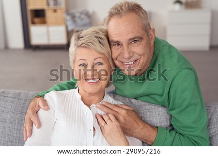 Close up Happy Portrait of a Sweet Senior Couple at the Living Room Couch, Smiling at the Camera - stock photo