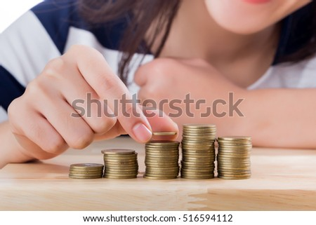 Close up happy woman with savings coins on table, finance concept.
