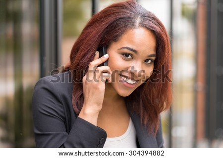 Close up Happy Young Afro-American Businesswoman Calling to Someone using her Mobile Phone Outside the Office While Smiling at the Camera. - stock photo