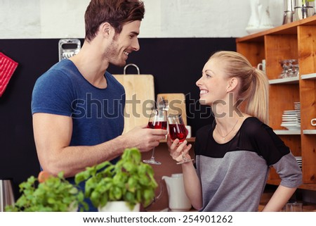 Close up Happy Young Couple Tossing Glasses of Wine While Staying at the Kitchen - stock photo