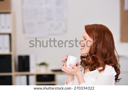 Close up Happy Young Woman Sitting at her Office Holding a Cup of Coffee Looking to the Left of the Frame. - stock photo