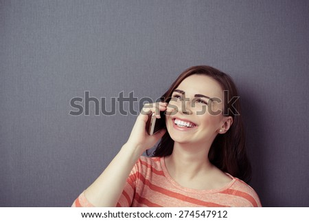 Close up Happy Young Woman Talking to Someone on Mobile Phone While Looking Up on a Gray Wall Background with Copy Space. - stock photo