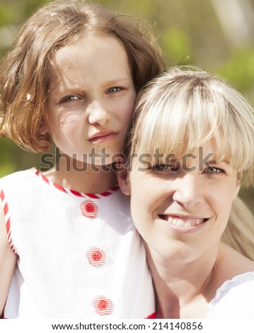 Close-up head shot of mother and daughter embracing - stock photo
