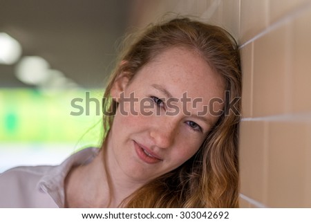 Close up headshot portrait of an attractive serious pensive young woman leaning against a tiled exterior wall look intently at the camera with a quiet smile - stock photo
