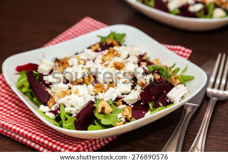close-up health-giving beet salad with arugula, feta cheese and walnut - stock photo