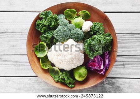 Close up Healthy Fresh Salad Ingredients with Broccoli, Cauliflower, Purple Cabbage and Brussels Sprout on Wooden Bowl, Placed on Wooden Table. - stock photo