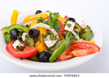 close up healthy greek salad in white bowl