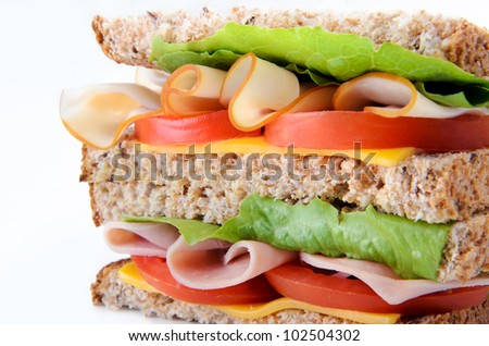 Close up healthy sandwich cross-section with ham and turkey with salad - stock photo