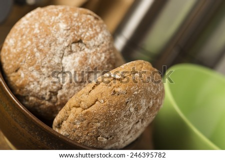 Close up high angle view of two freshly baked brown wholewheat rolls in a bowl on a kitchen counter - stock photo