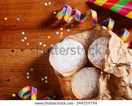 Close up Homemade Carnival Donuts with Powdered Sugar on Paper on Top of Wooden Table - stock photo