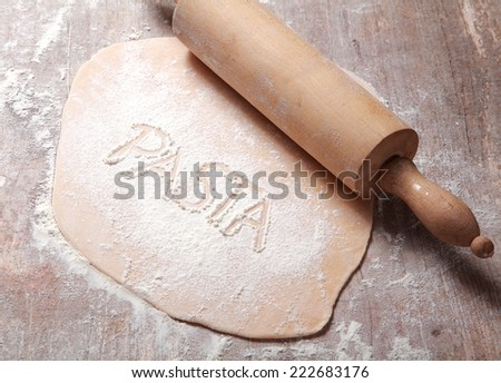 Close up Homemade Fresh Flattened Fettuccine Dough, Rolled by Wooden Dough Roller, Prepared on Wooden Table with Flour. - stock photo