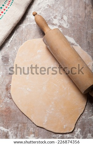 Close up Homemade Raw Fresh Pasta Flattened by Wooden Roller on Wooden Table with Flour. - stock photo