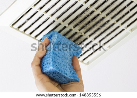 Close up horizontal photo of female hand cleaning dirty bathroom fan vent cover with blue sponge - stock photo