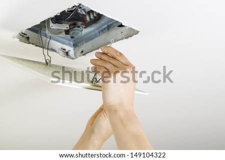 Close up horizontal photo of female hands installing clean bathroom fan vent cover from ceiling  - stock photo