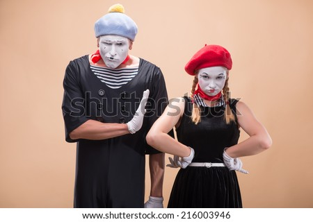 Close-up horizontal portrait of couple of two funny mimes, female mime  looking irritating at the camera and male mime showing her sign Stop isolated on beige background with copy place - stock photo