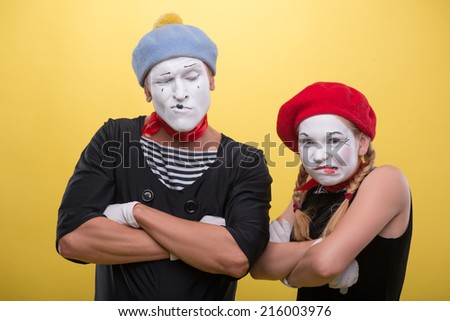 Close-up horizontal portrait of couple of two funny mimes holding their hands on their chest isolated on yellow background with copy place - stock photo