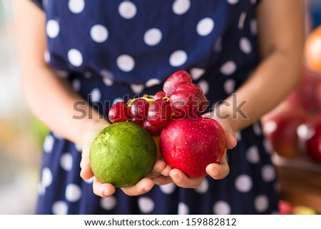 Close-up human hands holding fresh fruits on the foreground - stock photo