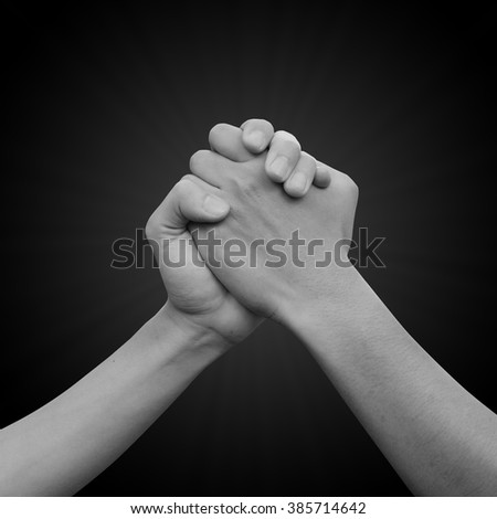 close up human handshake on black color background with soft sunbeam:man hands shake for confident,success,victory,assurance concept:trust and love of humanity conceptual idea.square frame picture - stock photo