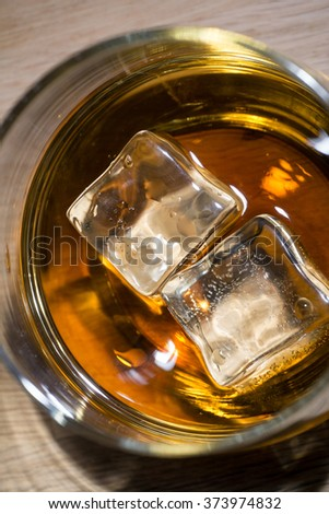 close up iced wiskey on wood floor from above